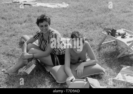 mother and sunbathing daughter on an inflatable lilo 1960s hungary - Stock Image