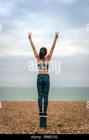 woman standing with arms raised on beach, back view, copyspace - Stock Image