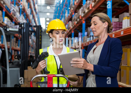 Warehouse manager with interacting female worker over digital tablet - Stock Image