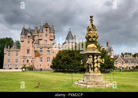 Front lawn of Glamis Castle with wild Ring-necked Pheasant and The Great Sundial with 80 sundials on top and 4 held by Lions Scotland UK - Stock Image