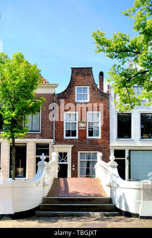 Delft, Holand-May 31, 2019: Canal house in Delft and beautiful white bridge on the Voorstraat .The house is  called 'De vergulde noot' that means the  - Stock Image