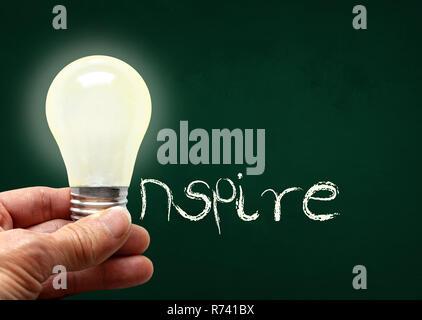 Man holding illuminated bulb with bare hands against chalkboard with the word Inspire. Concept of bright idea, innovation, imagination, inspiration, v - Stock Image