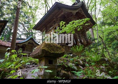 Low angle shot of Japanese stone lantern with Massha Kumano Shinto shrine in the background. Aomori prefecture, North Honshu, Japan. - Stock Image
