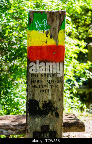 A wooden post with yellow green and red paint at the top informing people Emperor Haile Selassie walked here during his exile - Stock Image