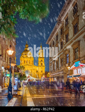 Budapest, Hungary - Snowy night at a Christmas market and shopping street with festive decoration, street-lamp and St.Stephen's basilica at background - Stock Image