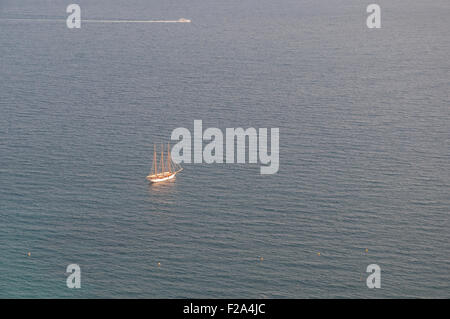 A lone sailboat in the Mediterranean Sea taking in the setting sun. - Stock Image