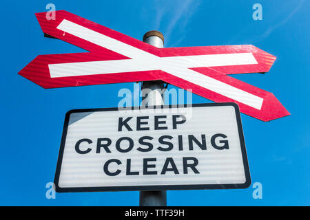 A level crossing (where a road crosses a railway line) signpost, with the notice – Keep crossing clear, against a blue sky. Norfolk, England, UK. - Stock Image