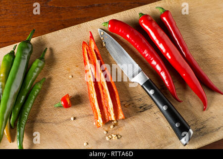 Deseeding Red and green hot chilli peppers on a carving board with knife - Stock Image