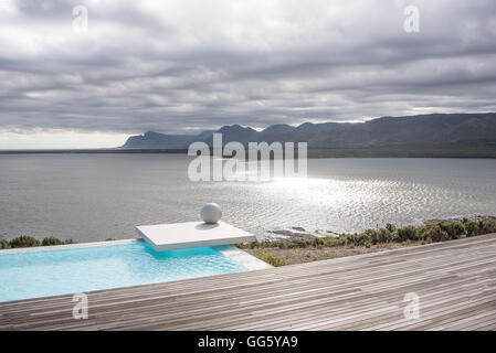 View of infinity pool at lakeside - Stock Image