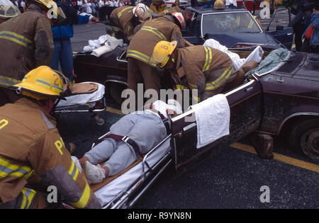 firefighters remove an injured person r esult of an auto accident - Stock Image