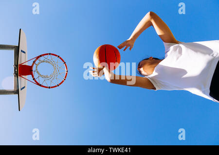 Young female basket player throwing the ball to the basket against a blue sky. Low angle view - Stock Image