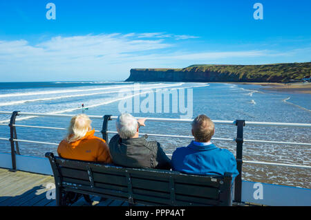 A  lady and two men  sitting on Saltburn Pier looking south towards Huntcliff and watching the surfers - Stock Image
