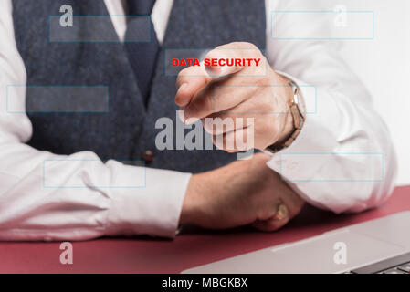 Business man sitting at desy pressing a virtual button saying data security. - Stock Image