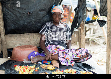 Adzopé, côte d'ivoire - June 10, 2017: old woman seated with legs bent, in black and white tee shirt, head attached by a scarf, sells her merchandise  - Stock Image