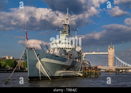 HMS Belfast tourist attraction ship, moored on River Thames in late afternoon sunlight, with Tower Bridge and London Red Bus crossing London SE1 - Stock Image