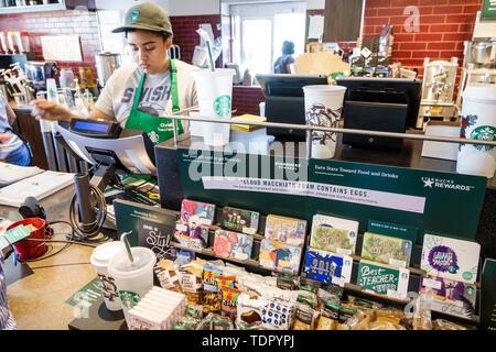 Fort Ft. Myers Florida Starbucks Coffee inside barista cashier reloadable payment cards snacks Black girl teen - Stock Image