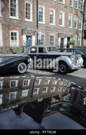 A 1964 Empress Bentley and a 1954 Rolls-Royce Silver Dawn are parked in Smith Square, a small square behind the Houses of Parliament, before collecting their VIP passengers - barristers who are being sworn in as QCs (aka Silks in legal vernacular), on 11th March 2019, in London, England. - Stock Image