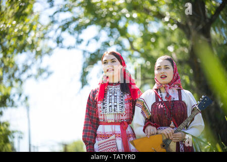 Two young women in traditional russian clothes walk holding hands and singing - midle shot - Stock Image
