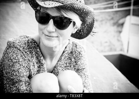 Beautiful black and white romantic portrait with blonde young caucasian woman sitting and hugging her nkees outdoor with sunglasses and little smile - Stock Image