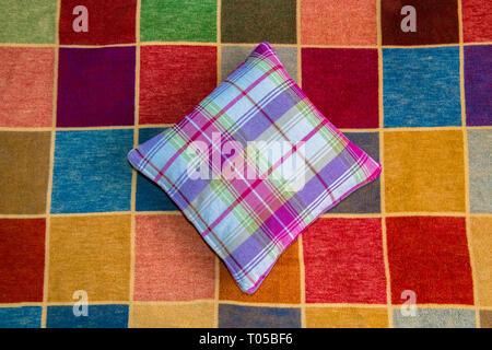 Tartan covered cushion on a multi coloured squared rug. - Stock Image