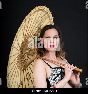 Young Woman with Chinese Parasol on a black background - Stock Image