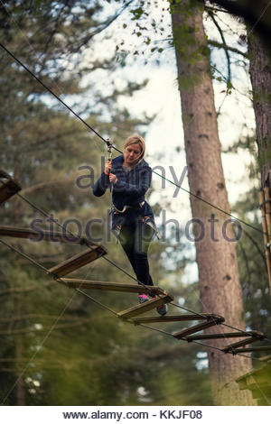woman on rope bridge - Stock Image