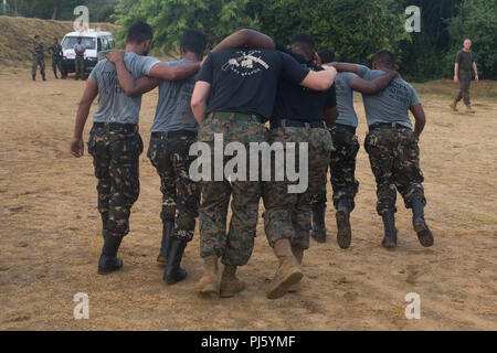 Sri Lanka – U.S. Marines and Sailors with the 13th Marine Expeditionary Unit (MEU) conduct physical training with Sri Lanka Navy Marines while on a regularly scheduled deployment of the Essex Amphibious Ready Group (ARG) and 13th MEU, August 25, 2018. The San Antonio-class amphibious transport dock USS Anchorage (LPD 23) and the embarked Marines of the 13th MEU conducted a theater security cooperation exercise with the Sri Lankan Navy and Navy Marines.  Part of a growing U.S.-Sri Lanka naval partnership, the exercise was also an opportunity for U.S. Seventh Fleet to explore local logistics sup - Stock Image