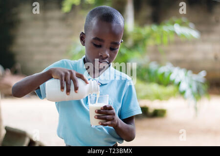 A child standing outside pours milk into a glass he holds in his hand. - Stock Image