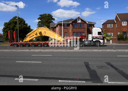 A heavy piece of machinery being transported on a low  loader trailer on the way to Southampton Docks. - Stock Image