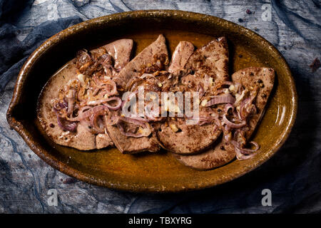 high angle view of higado encebollado, a spanish recipe of cow liver similar to liver and onions, served in a brown earthenware casserole - Stock Image
