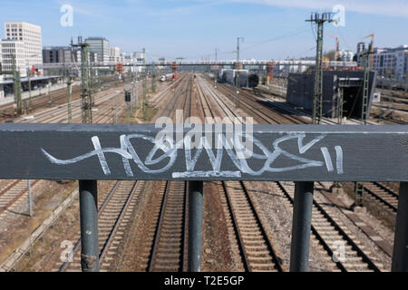 View towards main station in Munich with trails and power supply lines and graffiti in foreground - Stock Image