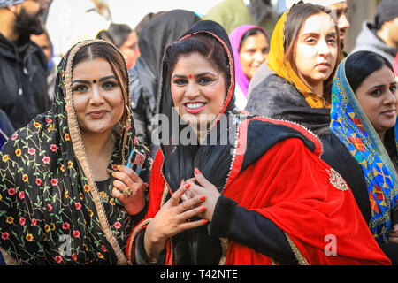 Gravesend, Kent, UK, 13th April 2019. Two women dressed in beautiful saris. Thousands of spectators and religious visitors line the streets of Gravesend in Kent to watch and participate in the annual Vaisakhi procession. Vaisakhi is celebrated by the Sikh community all over the world. - Stock Image