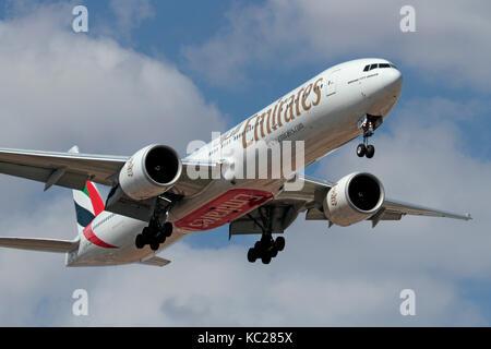 Long haul air travel. Emirates Boeing 777-300ER widebody passenger jet on approach - Stock Image