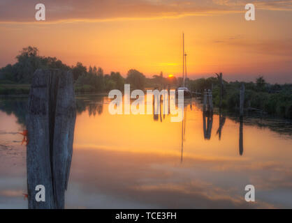 Boat moored on a river at sunset, Italy - Stock Image