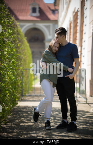 A young happy couple traveling. Standing on the street and hug. Mid shot - Stock Image