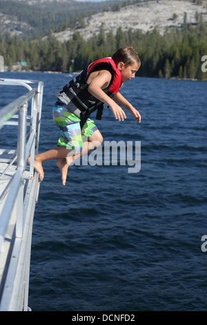 Young boy jumping off boat into lake - Stock Image
