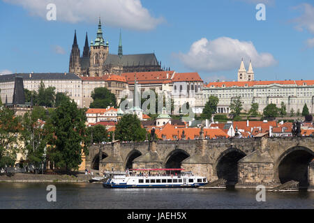 A boat passes under Charles Bridge with Prague Castle rising above in the background, Prague, Czech Republic - Stock Image