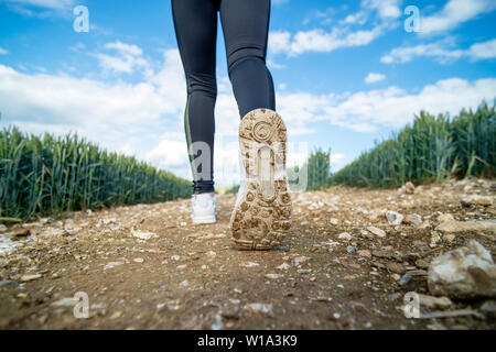 close up of the sole of a pair of sports trainers, jogging cross country. - Stock Image