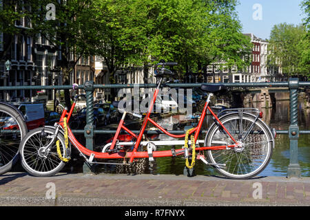 Tandem bike parked on a canal bridge in Amsterdam, Netherlands - Stock Image