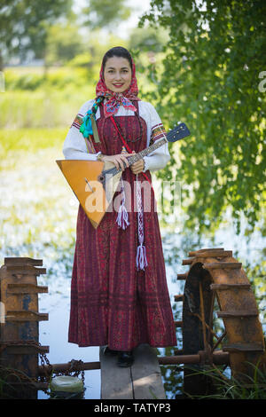 Young smiling woman in traditional russian clothes stands on a small bridge near the lake, and holding balalaika, vertical view - Stock Image