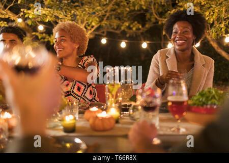 Happy friends enjoying dinner garden party - Stock Image