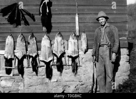 A young man poses with a selection of animal pelts on a barn side, ca. 1925. - Stock Image