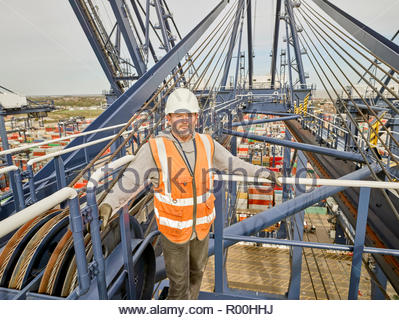 Dock supervisor on crane above cargo ship at the end of long walkway ship - Stock Image