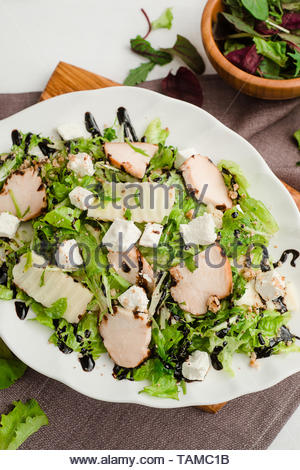 Salad with chicken breast, arugula, lettuce, homemade cheese and balsamic sauce. Cafe menu on a wooden background in warm colors with copy space. - Stock Image