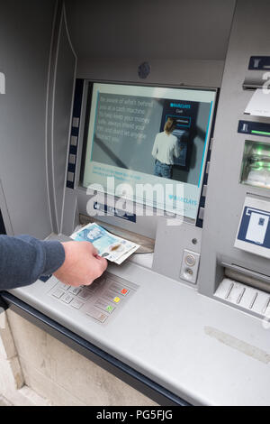 A woman removes £5 and £10 notes from an outside Barclays Bank, hole in the wall, cash point machine - Stock Image