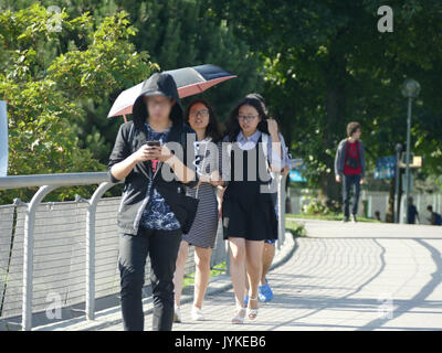 Germany Munich Olympia center Asian family tourists boy watching smartphone for SMS - Stock Image