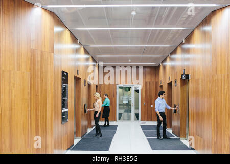 Young coworkers on corridor - Stock Image