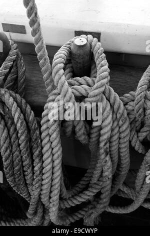 Belaying pins with coiled ropes on a tall ship. - Stock Image