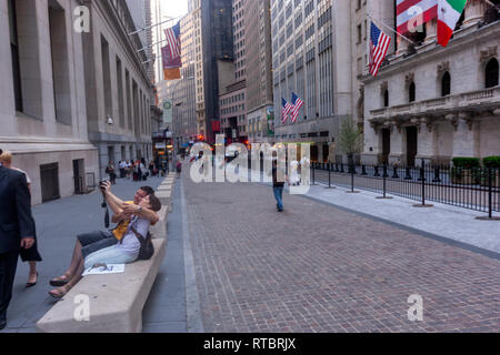 Couple taking a selfie with the American flag in the Stock Exchange, Wall Street, Manhattan, New York USA - Stock Image