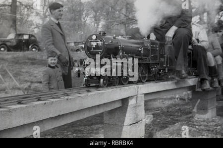 1950s, historical, father and young son looking at people riding on a little or model steam train or locomotive on an elavated, above-ground miniature railway, England, UK. - Stock Image